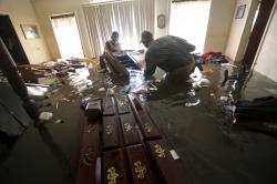 Paul England Jr., right, helps Michael Brown move bedroom furniture floating in his flooded home in the aftermath of Tropical Storm Harvey, in Port Arthur, Texas.