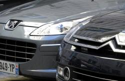 In this Sept. 7, 2012 file photo, a Peugeot, left, and Citroen cars are parked in Paris