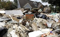 In this Sunday, Sept. 3, 2017, file photo, a garage sale sign stands in a pile of debris damaged by floodwaters in the aftermath of Hurricane Harvey in Spring, Texas