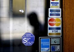 In this July 18, 2012, file photo, a pedestrian walks past credit card logos posted on a downtown storefront in Atlanta