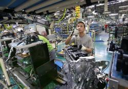 In this Aug. 2, 2017, photo, Nissan Motor Co. factory workers check engines on an assembly line at its plant in Yokohama, near Tokyo