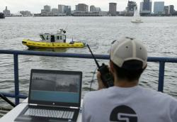 In this Aug. 15, 2017 photo, computer scientist Mohamed Saad Ibn Seddik, of Sea Machines Robotics, uses a laptop to guide a boat outfitted with sensors and self-navigating software and capable of autonomous navigation in Boston Harbor
