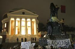 "Protesters cover a statue of Thomas Jefferson with black tarp and hold signs up in front of the Rotunda at the University of Virginia for the one month anniversary of the ""Unite the Right"" rally in Charlottesville Tuesday, Sept. 12, 2017"