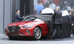 Sang Yup Lee, a head of Genesis Styling, left, and Luc Donckerwolke, a head of Genesis Design Center, second from right, unveil the new sedan Genesis G70 during its an unveiling ceremony in Hwaseong, South Korea, Friday, Sept. 15, 2017