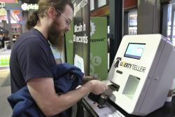 In this Monday, March 31, 2014, file photo, Tim McCormack, of Boston, inserts cash into a Liberty Teller ATM while purchasing bitcoins at South Station train station, in Boston.