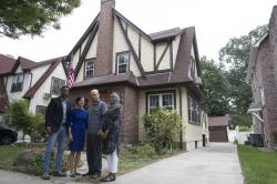 Abdi Iftin, left, of Somalia, Uyen Nguyen, second from left, of Vietnam, Eiman Ali, right, of Somalia born in Yemen, and Ghassan al-Chahada, of Syria pose for a photo outside President Donald Trump's boyhood home
