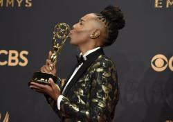"Lena Waithe poses in the press room with the award for outstanding writing for a comedy series for the ""Master of None"" episode ""Thanksgiving"" at the 69th Primetime Emmy Awards."