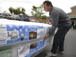 In this Feb. 27, 2012, file photo, Chris Kraft loads a new mattress set that he purchased at Costco Wholesale store in Glendale, Calif.