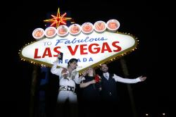 Elvis tribute artist Eddie Powers poses for a photo with newlyweds Rob and Kelly Roznowski after he married them at the Welcome to Las Vegas sign in Las Vegas.