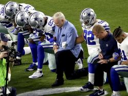 In this Monday, Sept. 25, 2017, file photo, the Dallas Cowboys, led by owner Jerry Jones, center, take a knee prior to the national anthem and an NFL football game against the Arizona Cardinals, in Glendale, Ariz.