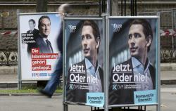 A person passes posters of the right-wing Freedom party, FPOE, and the conservative Austrian People's Party, OEVP, from left, in Vienna, Austria.