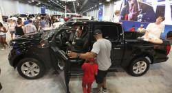 In this Monday, Oct. 9, 2017, photo, fairgoers look at pickup trucks on display at the State Fair of Texas in Dallas