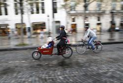 In this Sept.25, 2016 file photo, a woman and a man ride their bicycles on the Champs Elysees avenue during the 'day without cars,' in Paris