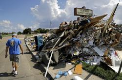 Wayne Christopher walks by a pile of debris outside the church he'd attended his whole life damaged from Hurricane Harvey in Port Arthur, Texas, Monday, Sept. 25, 2017