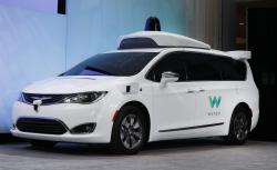 In this Sunday, Jan. 8, 2017, file photo, a Chrysler Pacifica hybrid outfitted with Waymo's suite of sensors and radar is displayed at the North American International Auto Show in Detroit
