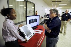 In this Thursday, Oct. 19, 2017 photo, Renee Phifer, Rockdale County board of elections assistant director, left, demonstrates a new voting machine at a polling site to Kelly Monroe, investigator with the Georgia secretary of state office in Conyers, Ga.