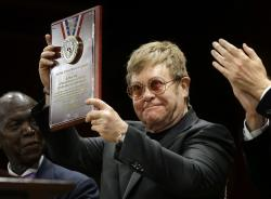 Elton John holds up the 2017 Harvard Humanitarian of the Year Award