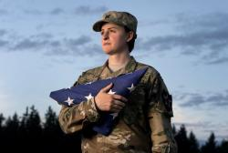 Capt. Jennifer Peace holds a flag as she stands for a photo near her home in Spanaway, Wash