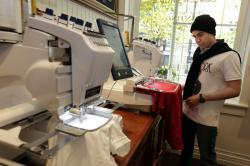 Alexander Gentil checks custom embroidery in progress at the Polo Ralph Lauren store, in New York's SoHo neighborhood.