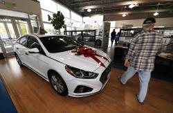 In this Friday, Oct. 6, 2017, file photo, a buyer walks past a 2018 Sonata sitting amid an assortment of models on the showroom floor of a Hyundai dealership in the south Denver suburb of Littleton, Colo.