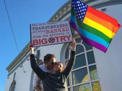 Nick Rondoletto, left, and Doug Thorogood, a couple from San Francisco, wave a rainbow flag and hold a sign against a proposed ban of transgendered people in the military at a protest in the Castro District.