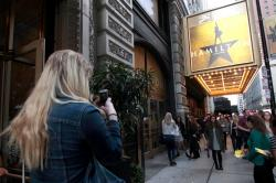 "In this photo taken Oct. 4, 2017, Alex Richards takes a photo of Meera Ganesh outside the CIBC Theatre after watching ""Hamilton: An American Musical"" in Chicago."