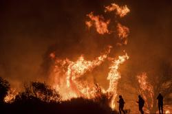 Motorists on Highway 101 watch flames from the Thomas fire leap above the roadway north of Ventura, Calif.