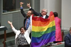 Members of parliament, from left, Cathy McGowan, Adam Brandt and Andrew Wilkie celebrate the passing of the Marriage Amendment Bill in the House of Representatives at Parliament House in Canberra.