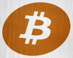 In this Monday, April 7, 2014, file photo, a bitcoin logo is displayed at the Inside Bitcoins conference and trade show in New York