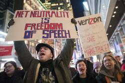 Dmonstrators rally in support of net neutrality outside a Verizon store in New York.