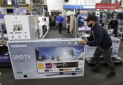 Jesus Reyes pushes a television down an aisle as he shops a Black Friday sale at a Best Buy store.