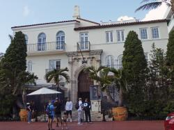 Tourists pose for photographs and read a restaurant menu in front of The Villa Casa Casuarina, a boutique hotel that once was the home of fashion designer Gianni Versace in Miami Beach, Fla.