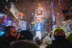 People celebrate New Year as confetti fall down after the countdown to midnight in Times Square during New Year's celebrations.