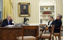 President Donald Trump speaks on the phone with Prime Minister of Australia Malcolm Turnbull, with then-National Security Adviser Michael Flynn, center, and then- chief strategist Steve Bannon, right, in the Oval Office of the White House in Washington.