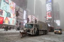 A snow plow clears snow off Broadway in New York's Times Square.