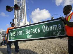 "In this Thursday, Dec. 17, 2015 file photo, Dale Moncur, left, and Cedric Anderson of Palm Beach County Traffic Operations, hold a sign for the new President Barack Obama Highway in preparation to change it from the ""Old Dixie Highway"" in Riviera Beach, Fla."