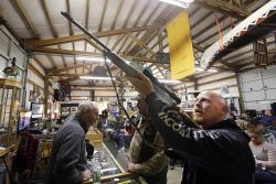 In this Oct. 20, 2017 photo, customer Andy Muscato looks over a rifle before an auction at Johnny's Auction House, where the company handles gun sales for several police departments and the Lewis County Sheriff's Office, in Rochester, Wash.