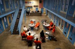 Inmates inside Albany County jail's veteran's pod gather for a group session with Sarah Polidore, center, executive director of field services for Moral Reconation Therapy, Monday, Nov. 27, 2017, in Albany, N.Y.