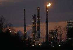 In this Feb. 13, 2015 file photo, stacks and burn-off from the ExxonMobil refinery are seen at dusk in St. Bernard Parish, La.