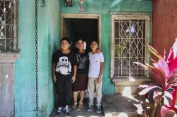 Flor Tovar and her two sons Christian, right, and Omar Elias, left, pose for a photo at their home in Ciudad Real, El Salvador, Tuesday, Jan. 9, 2018