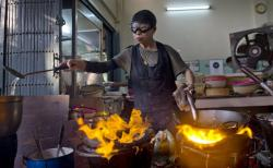 "Thai cook Supinya Jansuta, 72, better known as ""Jay Fai,"" wearing goggles, cooks with two flaming woks at her eatery in Bangkok, Thailand."