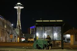 In this Oct. 30, 2017 file photo, Dave Chung, who says he has been homeless for five years on the streets of California and Washington state, eats a meal before bedding down in a bus shelter in view of the Space Needle in Seattle