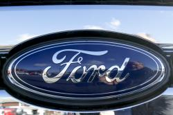 This Thursday, Nov. 19, 2015, file photo, shows the Ford badge in the grill of a pickup truck
