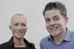 In this Sept. 28, 2017, photo, David Hanson, the founder of Hanson Robotics, smiles with his company's flagship robot Sophia, a lifelike robot powered by artificial intelligence, for a photo in Hong Kong