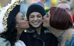 Actress Mia Kunis, center, is kissed by Amira Weeks, left, and Jacques Berguig during a parade for Kunis in Cambridge, Thursday, Jan. 25, 2018.