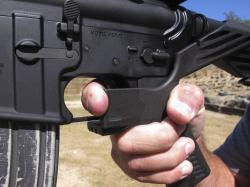 In this Oct. 4, 2017, file photo, shooting instructor Frankie McRae demonstrates the grip on an AR-15 rifle fitted with a bump stock at his 37 PSR Gun Club in Bunnlevel, N.C.