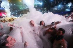 Partygoers dance in foam at The City nightclub in the Caribbean resort city of Cancun, Mexico.