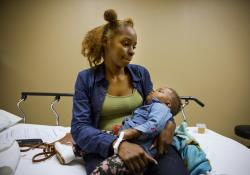 Delisah Revell holds her 10-month-old daughter Kelce who is being treated in the emergency room for the flu at Upson Regional Medical Center in Thomaston, Ga.,