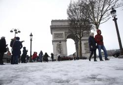 Tourists stroll on the snow-covered Champs Elysees avenue near the Arc de Triomphe in Paris, France, Friday, Feb. 9, 2018.