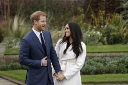 In this file photo dated Monday Nov. 27, 2017, Britain's Prince Harry and his fiancee Meghan Markle pose for photographers in the grounds of Kensington Palace in London.